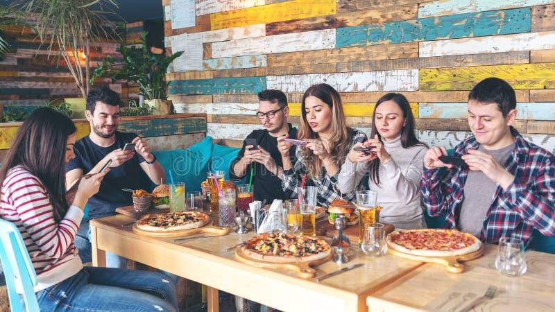 """Jovens que fotografam o alimento amigos felizes no †rústico do restaurante """"que tomam a imagem da pizza e dos Hamburger com tel foto de stock royalty free"""