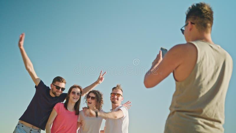 Jovens que levantam para uma foto na praia fotografia de stock royalty free