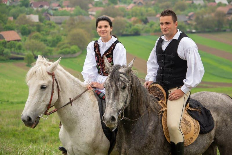 Jovens que montam em cavalos bonitos, tendo o divertimento nas horas de verão, campo de Romênia foto de stock