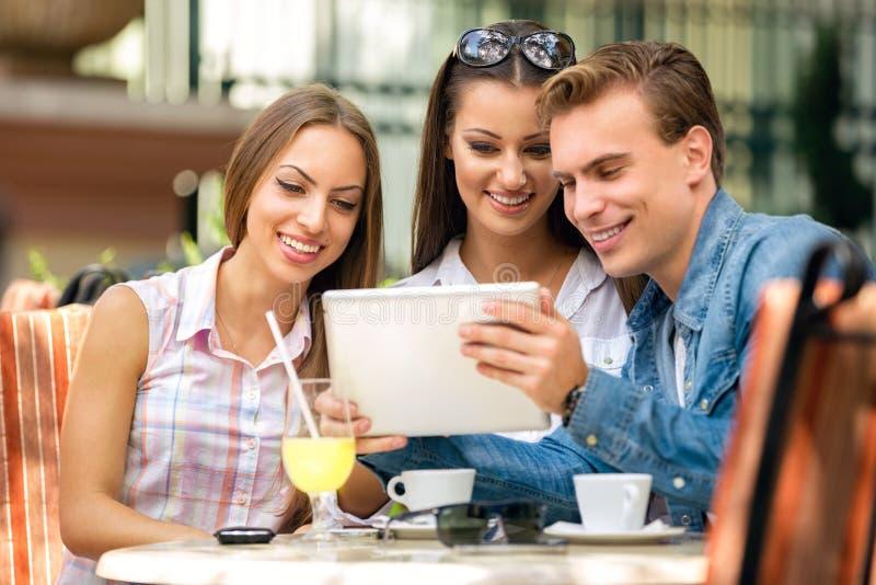 Jovens que olham o PC da tabuleta no café fora foto de stock