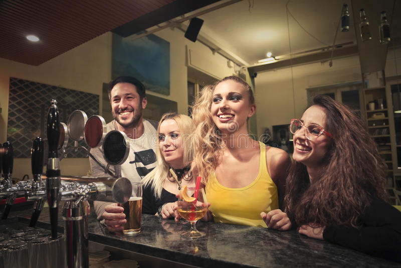 Jovens que têm o divertimento em um bar fotos de stock