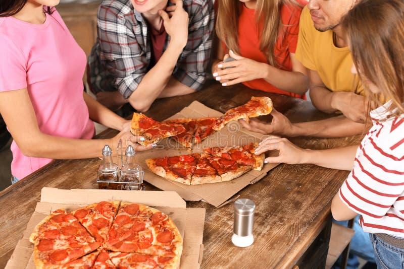 Jovens que têm o divertimento no partido com pizza deliciosa dentro fotografia de stock
