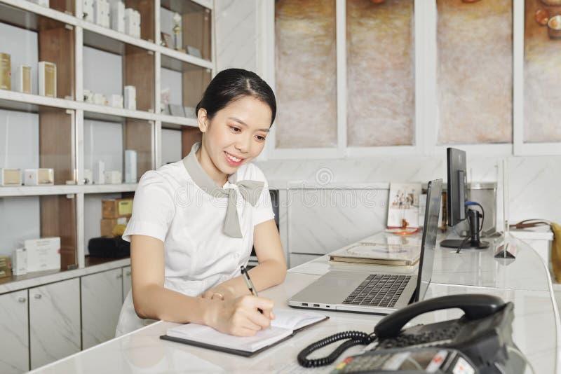 Jovens recepcionistas do salão sorridente Estão sorrindo a recepcionista vietnamita do salão de spa tomando notas no planejador imagem de stock