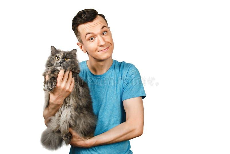 Jovens seguram um gato britânico cinzento sobre o fundo cinza claro fotografia de stock royalty free