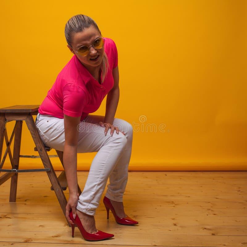 Jovens sofrem de desconfortáveis sapatos de salto alto, retrato no Studio sobre um fundo amarelo fotos de stock
