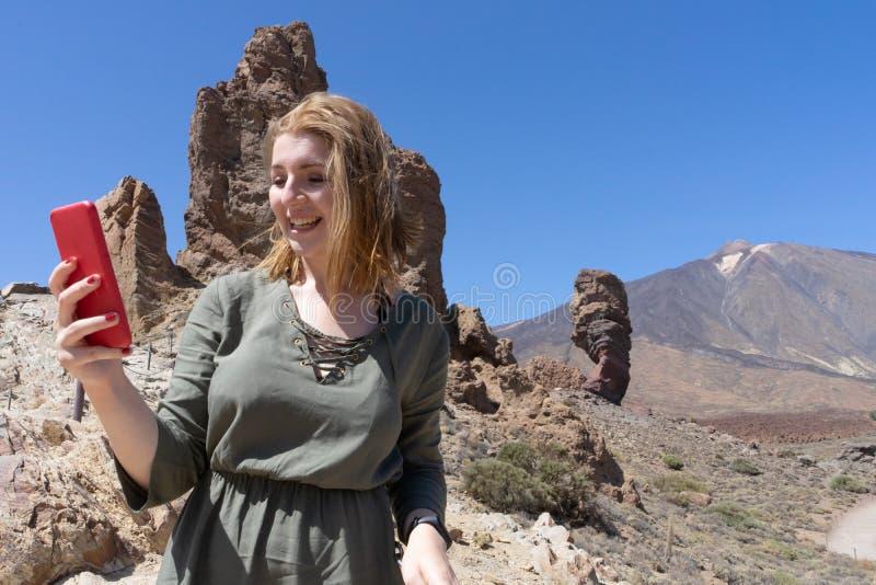 Jovens turistas brancos no parque nacional, segurando um smartphone procurando por sinal, sozinhos no deserto vulcânico remoto no imagens de stock royalty free