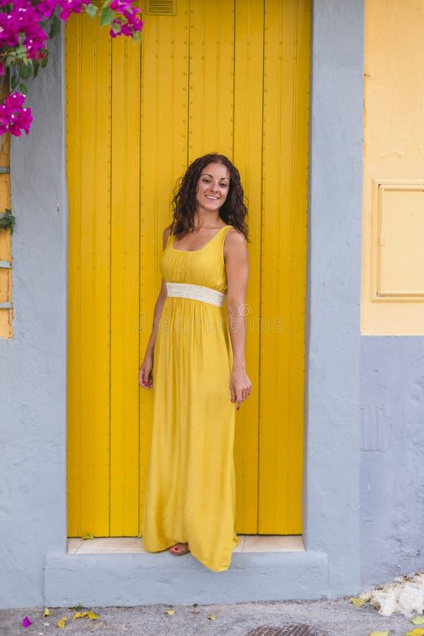 Jovens turistas de vestido amarelo sorrindo por uma porta amarela na cidade Portugal Conceito de viagem foto de stock