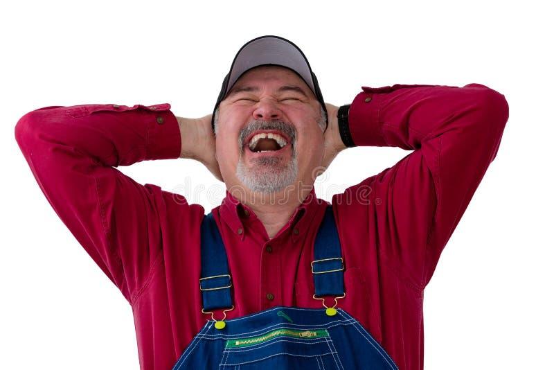 Joviaale landbouwer of arbeider die van een hartelijke lach genieten stock foto's
