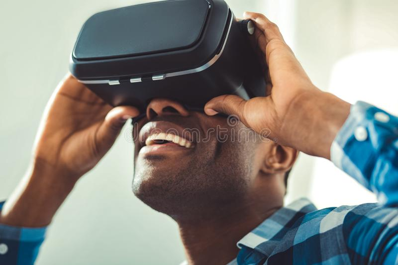 Jovial afro american man wearing VR glasses. Innovative technologies. Low angle of merry afro american man putting on VR glasses and tuning them royalty free stock images