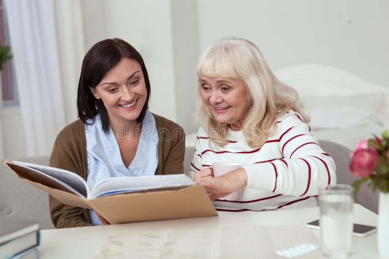 Jovial elder woman and caregiver scrutinizing photo album. Life history. Positive caregiver holding photo album while elder women sipping tea stock image