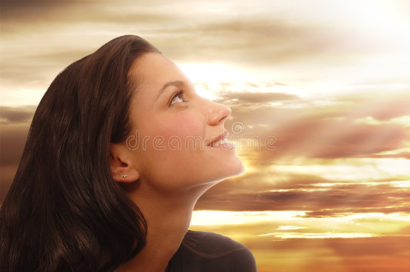 Joy. Beautiful young woman looking to heaven with a peaceful expression
