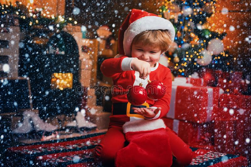 Joy and happiness. Childhood moments. Kid boy santa hold christmas gift red sock. Christmas stocking concept. Child stock photography