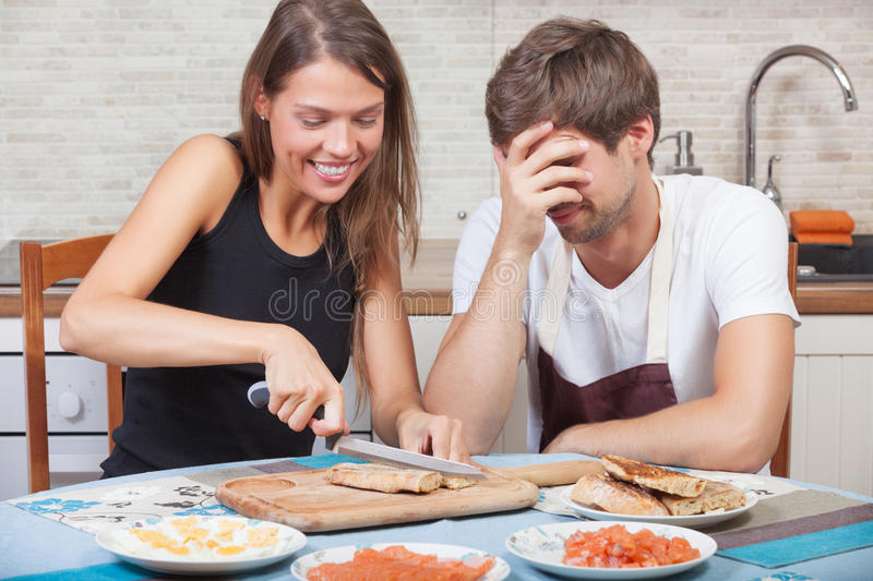 Joy on the kitchen. Couple having fun while preparing the dinner together stock photo