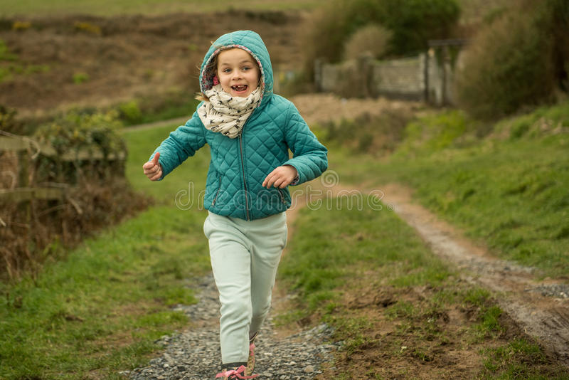 Joy. A little girl smiling while running royalty free stock photos