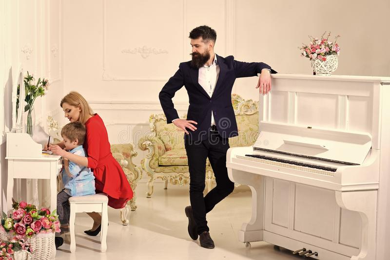 Joy of parenting. Home schooling concept. Father stands near piano, watching while mother teaches son preschooler to stock photos