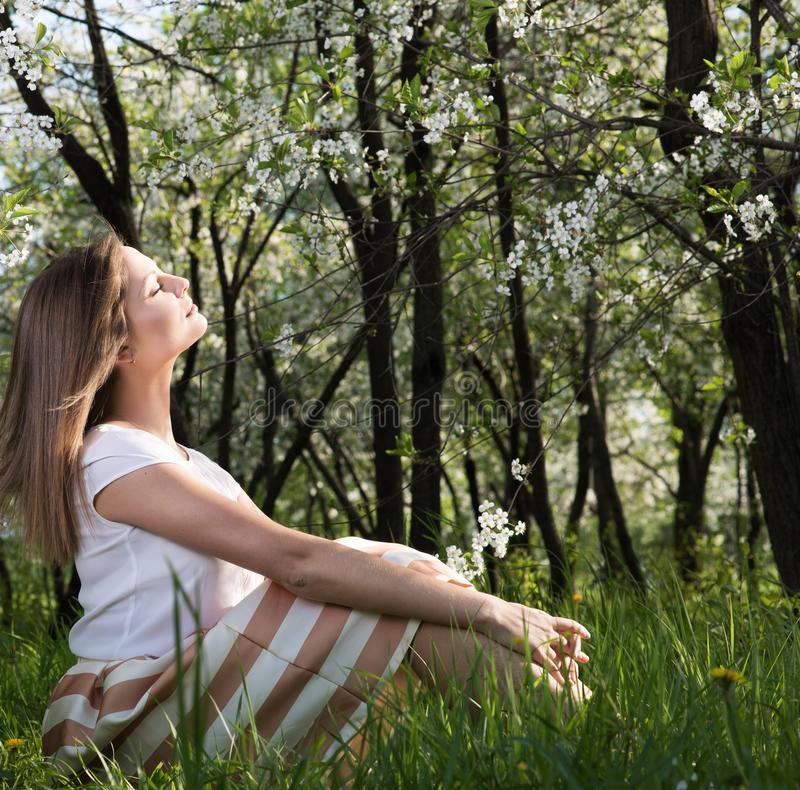 Joy spring sun. Attractive young woman sitting with eyes closed. In a lush garden on the grass. Spring mood stock photo