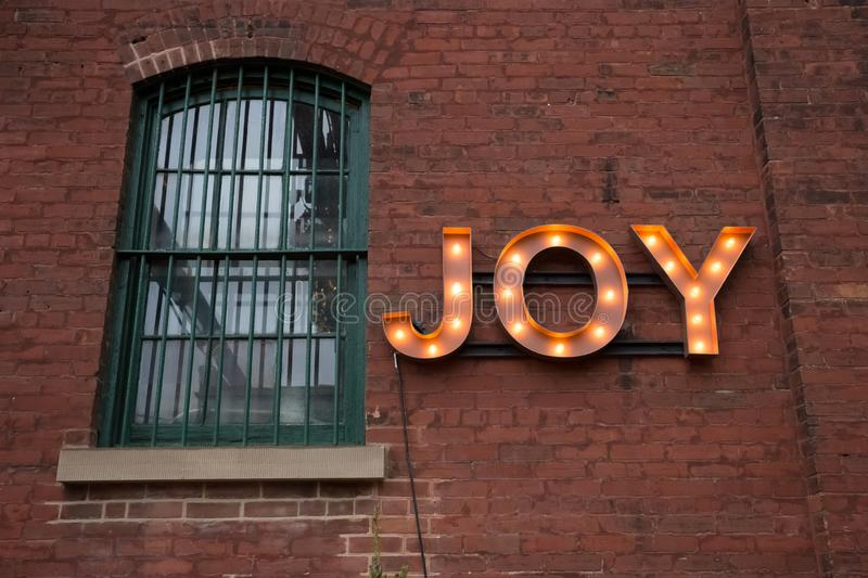 JOY Light Bulb Sign on Wall royalty free stock photography