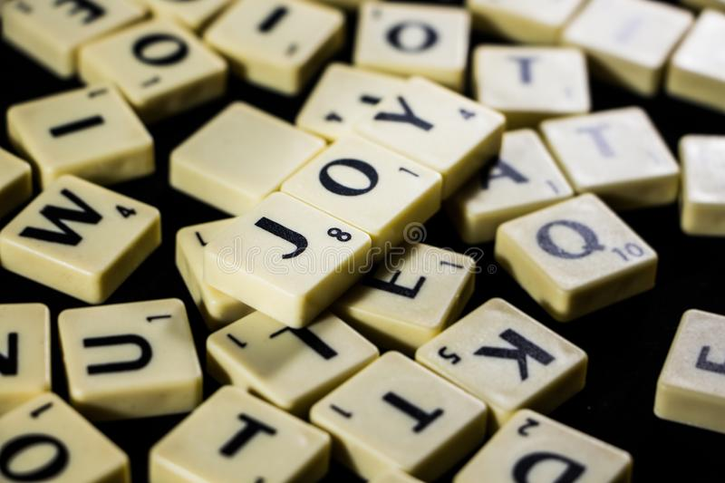 Joy word spelled with letter tiles in black background stock images