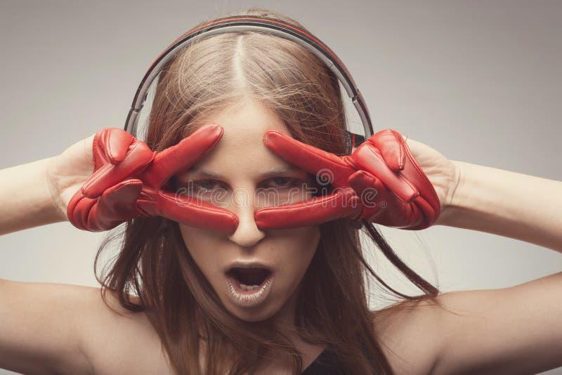 Joyable η ελκυστική μουσική ακούσματος κοριτσιών μόδας όμορφη με τα ακουστικά, που φορούν τα κόκκινα γάντια, παίρνει την ευχαρίστ στοκ εικόνες