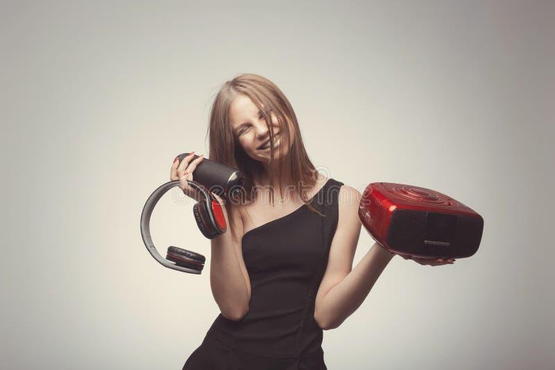 Joyable mody atrakcyjnej ładnej dziewczyny słuchająca muzyka z hełmofonami, mówcą, dokumentacyjnym graczem, mienia thm w rękach i fotografia royalty free