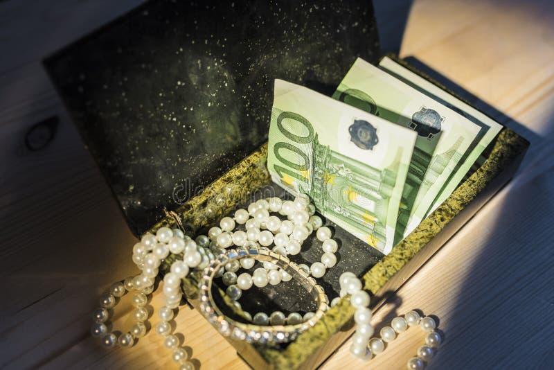 Joyas y dinero en la caja imágenes de archivo libres de regalías