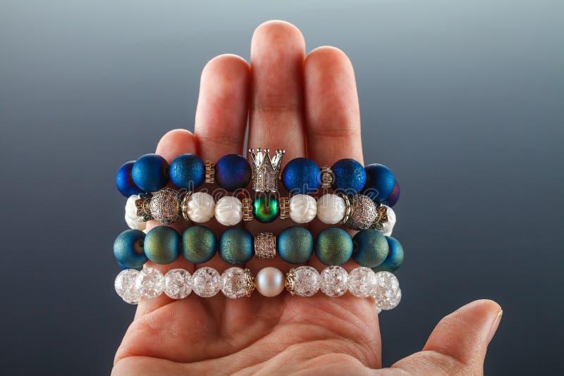Joyería hermosa hecha de piedras naturales y de accesorios exquisitos en la mano de una mujer imagen de archivo libre de regalías