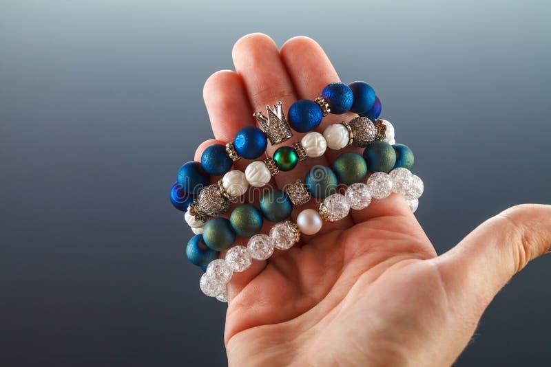 Joyería hermosa hecha de piedras naturales y de accesorios exquisitos en la mano de una mujer fotos de archivo libres de regalías