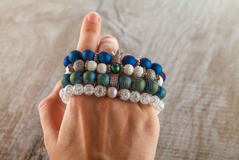 Joyería hermosa hecha de piedras naturales y de accesorios exquisitos en la mano de una mujer fotos de archivo