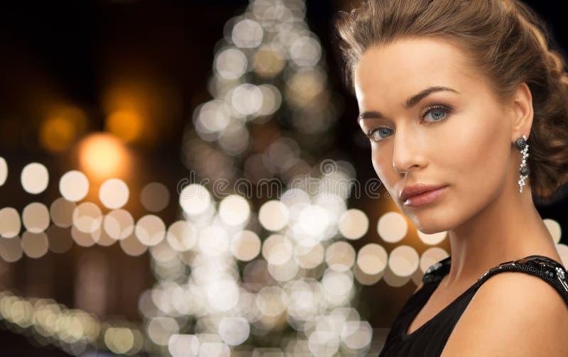 Joyería que lleva de la mujer sobre luces de la Navidad imagen de archivo libre de regalías