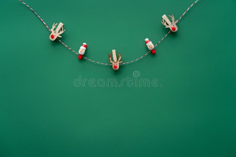 Joyeuse carte de Noël, drôles de rennes accrochés à la corde sur fond vert photo stock