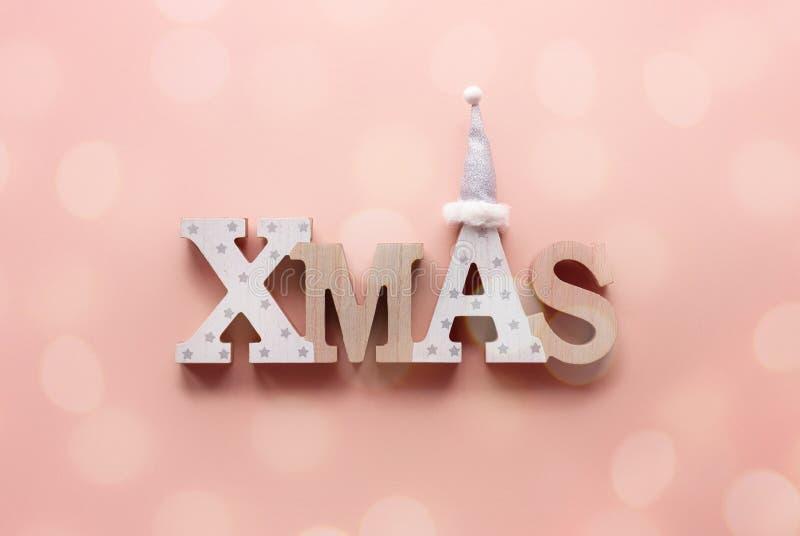 Joyeuse carte de Noël, lettres xmas s'affichent sur fond rose de livre minimal photos stock