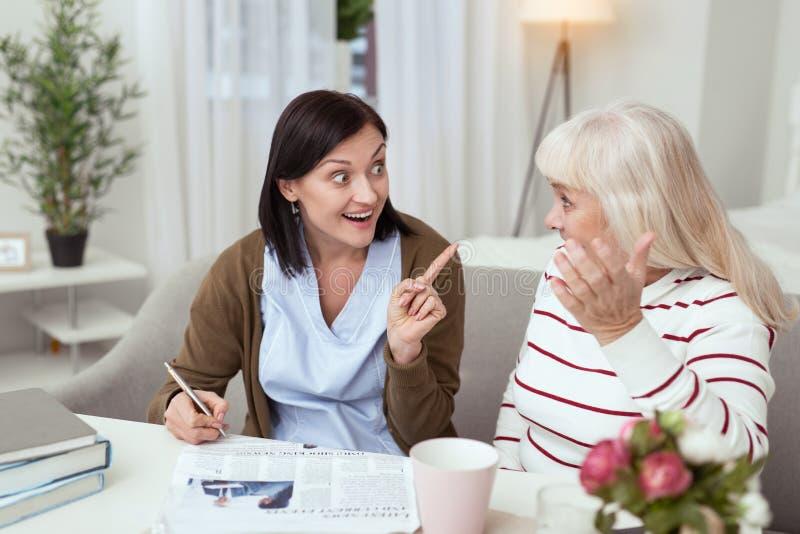 Joyeuse femme plus âgée et travailleur social résolvant des mots croisé photos stock
