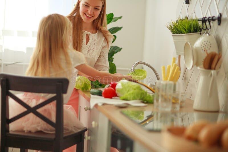Joyeuse jeune mère avec sa fille dans la cuisine lave les légumes dans l'évier, interaction des enfants et des parents à la maiso image libre de droits