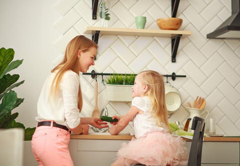Joyeuse jeune mère avec sa fille dans la cuisine lave les légumes dans l'évier, interaction des enfants et des parents à la maiso images libres de droits
