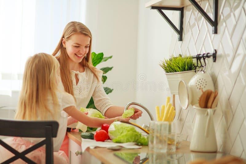 Joyeuse jeune mère avec sa fille dans la cuisine lave les légumes dans l'évier, interaction des enfants et des parents à la maiso image stock