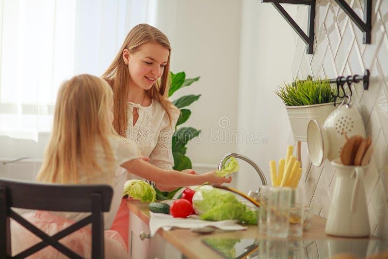 Joyeuse jeune mère avec sa fille dans la cuisine lave les légumes dans l'évier, interaction des enfants et des parents à la maiso photos stock