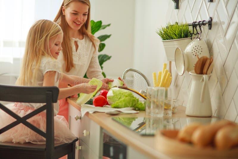 Joyeuse jeune mère avec sa fille dans la cuisine lave les légumes dans l'évier, interaction des enfants et des parents à la maiso photographie stock libre de droits