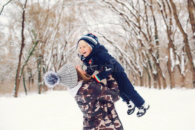 Joyeuse mère et enfant qui s'amusent sur une promenade d'hiver enneigée dans la nature Saison hivernale de froid Famille heureuse image stock