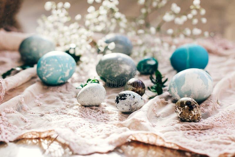 Joyeuses Pâques, carte de voeux Oeufs de pâques élégants avec des fleurs de ressort et branches vertes de buxus sur le tissu rust photos libres de droits