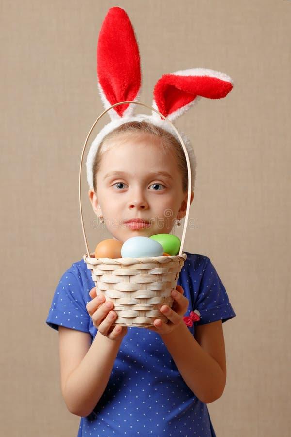 Joyeuses Pâques Fille d'enfant avec des oreilles et des oeufs de lapin image libre de droits
