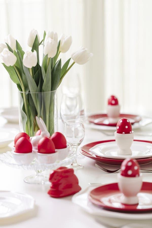 Joyeuses Pâques L'arrangement de décor et de table de la table de Pâques est un vase avec les tulipes et les plats blancs de coul photo libre de droits