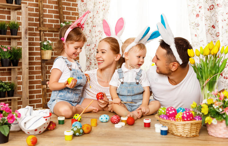 Joyeuses Pâques ! la mère, le père et les enfants de famille peignent des oeufs pour images libres de droits