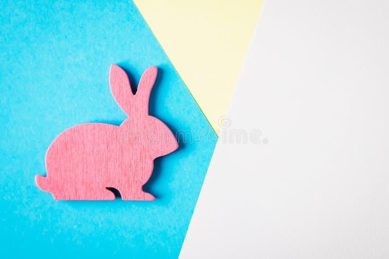 Joyeuses Pâques Lapin de Pâques en bois rose sur un fond bleu et blanc et jaune Photo créative à la mode image stock