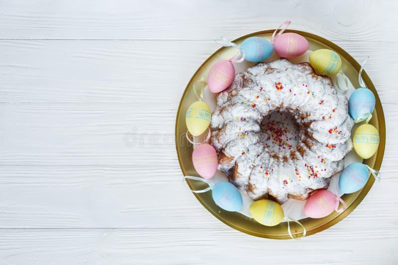 Joyeuses Pâques ! Plateau d'or avec le plat avec le gâteau et les oeufs colorés peints à la main, tulipes sur la table en bois bl images stock