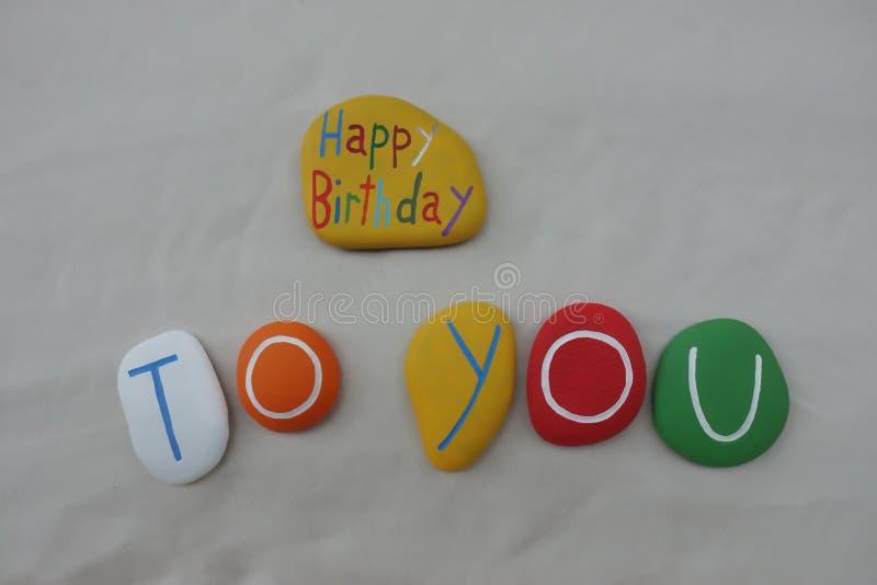 Joyeux anniversaire avec une composition colorée en pierres au-dessus du sable blanc image stock