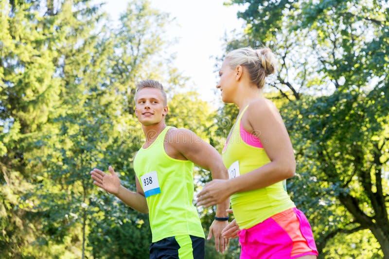 Joyeux couple de sportifs en course avec un numéro de badge photos libres de droits