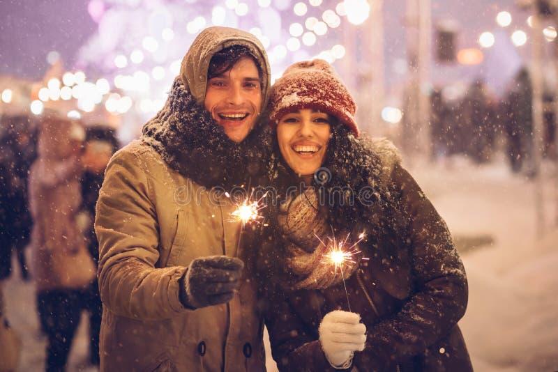 Joyeux couple tenant des lumières du Bengale debout en plein air la nuit photo stock