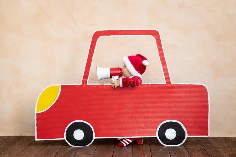Joyeux enfant costume du Père Noël jouant à la maison photos stock