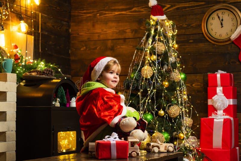 Joyeux enfant décorant le sapin de Noël Joyeux enfant mignon de Santa hat avec le présent a Noël Nouvel An Noël image libre de droits