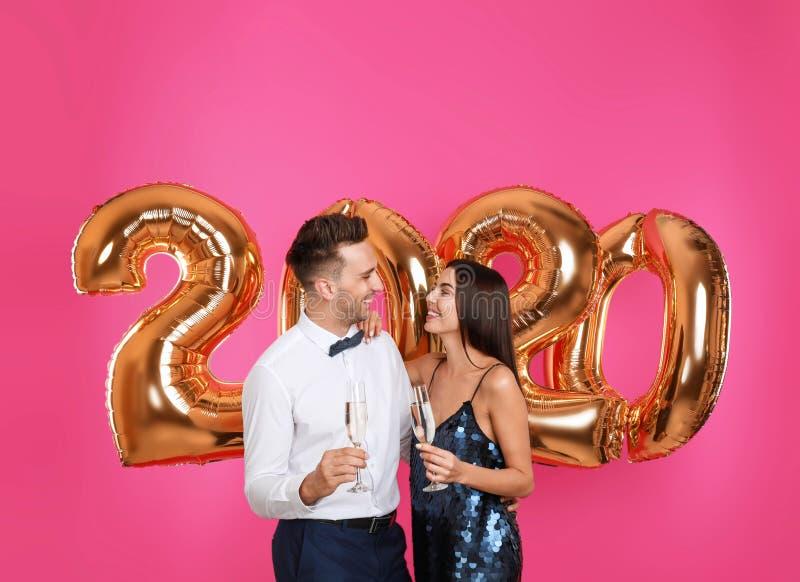 Joyeux jeune couple avec des lunettes de champagne près de ballons dorés 2020 sur fond rose image libre de droits
